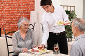 stock photo of clientele  - Senior couple being served food in a restaurant - JPG