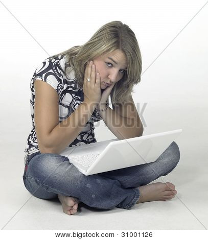 Bored Girl Sitting On The Floor With White Laptop