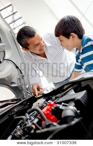 Father and son at the dealer looking at a car engine