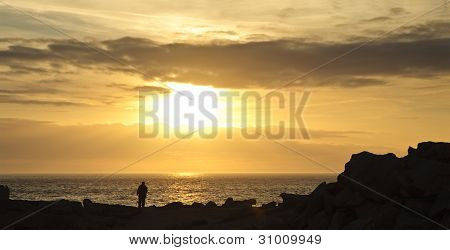Landscape Photographer Silhouette Against Rocky Cliffs And Stunning Vibrant Sunset Sky