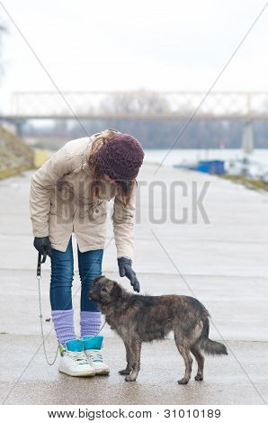 Pretty teenage girl with the dog on cloudy autumn day