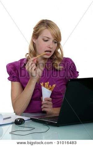 Woman clerk eating French fries at her desk