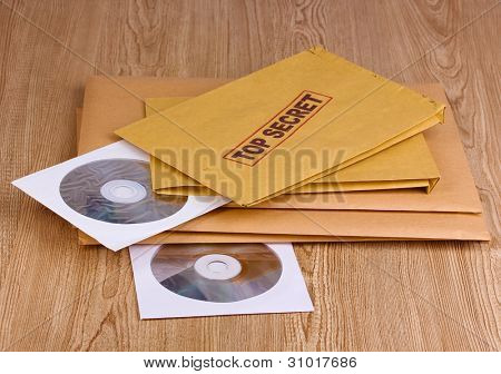 Envelopes with top secret stamp with CD disks on wooden background