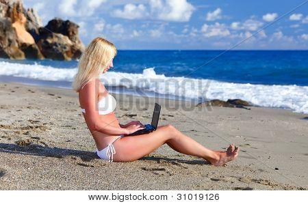 Sexy Beautiful Woman In Bikini Using Laptop At The Beach