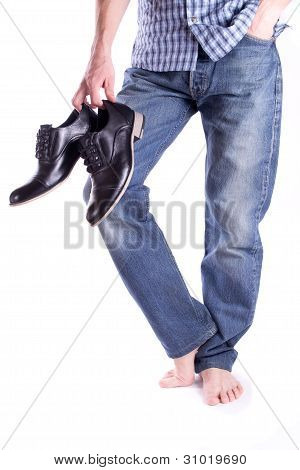Men's feet barefoot and holding a pair shoes