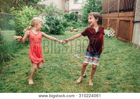 poster of Kids Friends Boy And Girl Splashing With Gardening Hose Sprinkler On Backyard On Summer Day. Childre