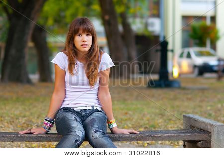 Pretty teenage girl sitting on the bench in the park on beautiful autumn day