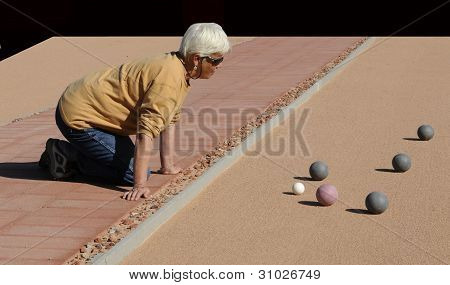 Senior Woman Studying Bocce Balls On Sand Court