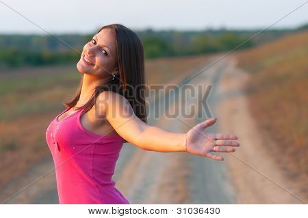Beautiful happy young girl smiles with spread arms while standing on the country road on sunny day