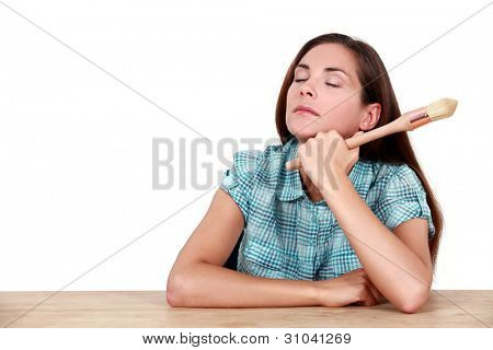 Sleepy woman holding paint brush