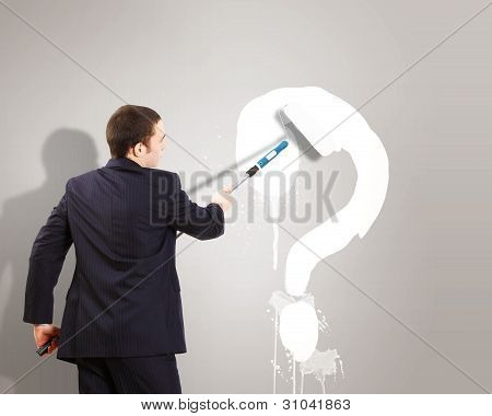 Businessman with paint brash and question mark