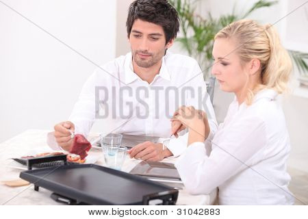 Couple cooking meat on hotplate