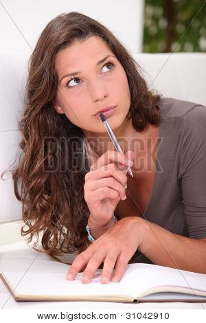 Young woman thinking about what to write in her book