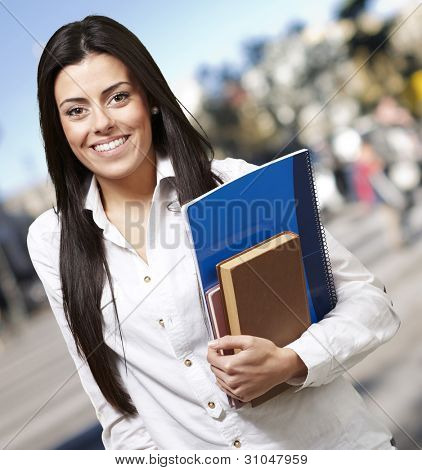 pretty young woman smiling and holding notebooks against a street background