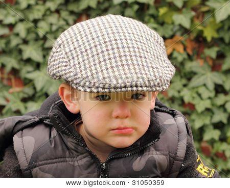 young boy wearing a flat cap