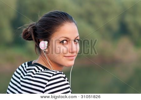Pretty smiling teenage girl listens to music while enjoying autumn nature