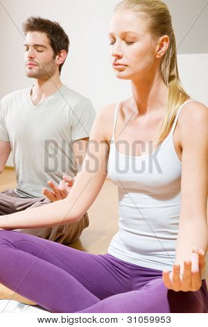Couple Sitting On Floor Doing Yoga