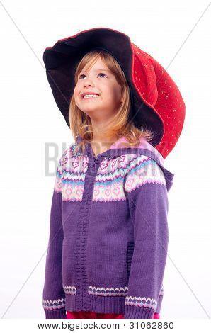 Sorridente menina bonito com chapéu de assistentes na cabeça olhando para cima
