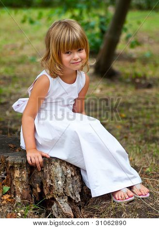 Beautiful little girl smiles while posing outside