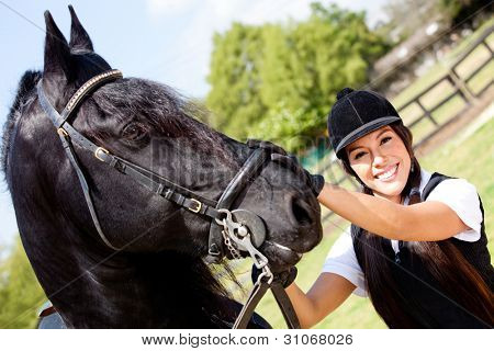 Portrait of a female jockey with a horse outdoors