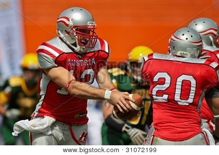 VIENNA, AUSTRIA - JULY 15: QB Thomas Haider (#13 Austria) hand off the ball to RB Mario  Nerad (#20 Austria) at the Football World Championship on July 15, 2011 in Vienna, Austria.