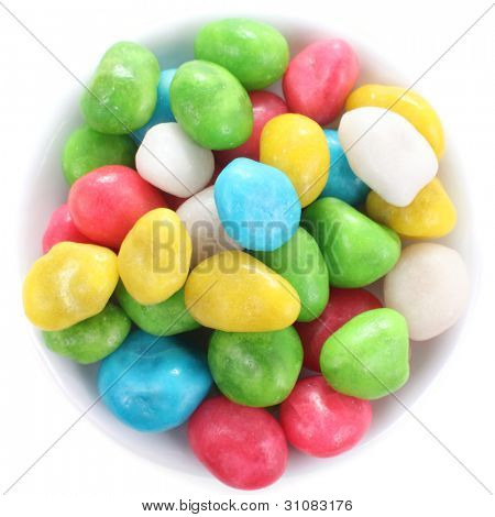 Multicolored candies on a little-little plate close up, isolated over white