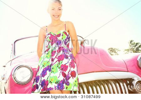 Vintage woman and car. Old retro style car and beautiful young happy smiling woman on road trip. Pretty mixed race Caucasian / Asian Chinese female lifestyle model. Photo from Havana, Cuba.