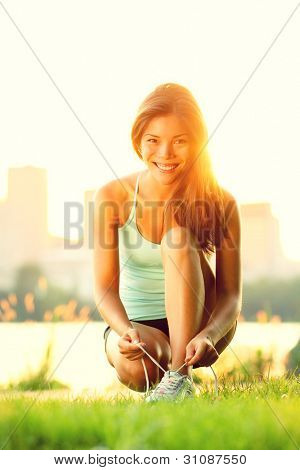 Woman running workout in sunshine on sunny summer day. Beautiful young sport fitness model getting ready for jogging in city park. Mixed race girl.