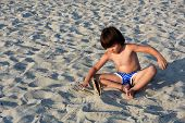 Little Boy Play In The Sand On Beach. Happy Child Playing In The Sand poster
