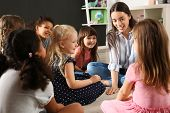 Cute Little Children With Nursery Teacher In Kindergarten. Indoor Activity poster