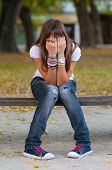 Young girl in fashionable warn out jeans, snickers and t-shirt hides her face