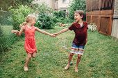 Kids Friends Boy And Girl Splashing With Gardening Hose Sprinkler On Backyard On Summer Day. Childre poster