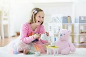Little Girl Playing With Doll House. Kid With Toys poster