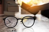 Focus At Glasses And Background Of Woman Sitting In A Cafe, Reading Book. poster