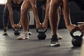 Closeup of young man and fit woman hands lifting kettle bell while squatting at gym. Athlete people  poster