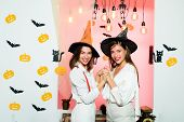 Happy Young Women In Witch Halloween Costumes On Party Over Isolated Background. Halloween Dresses A poster