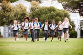 Excited Elementary School Pupils Wearing Uniform Running Across Field At Break Time poster