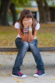 stock photo of snickers  - Young girl in fashionable warn out jeans - JPG