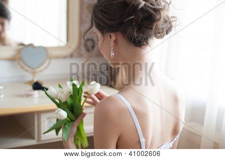 Portrait of young beautiful bride with bouquet of white tulips preparing to her wedding day