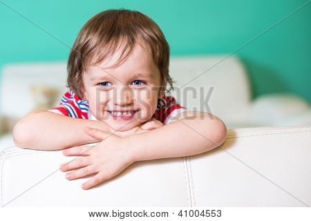 Happy Smiling Little Child Boy Sitting On A Sofa