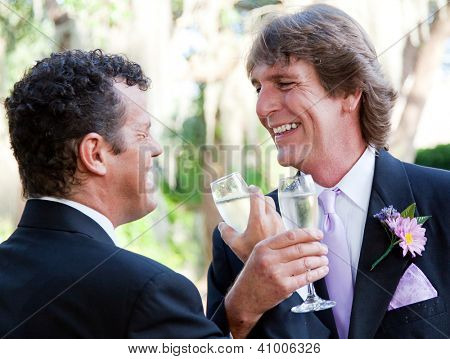 Handsome gay couple at their wedding, toasting with champagne.
