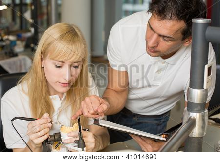 Instructor Teaching An Apprentice In Dental Lab
