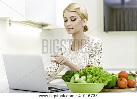 Young Woman Looking For A Recipe On The Laptop Computer In The Kitchen.