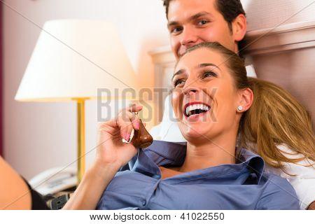 Jovem casal deitado na cama no quarto do hotel e a mulher tem uma chave na mão