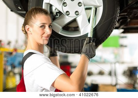 Young woman as female car mechanic working on an auto in workstation