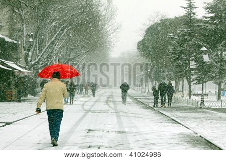 A pedestrian uses a red umbrella to shield himself from snowfall