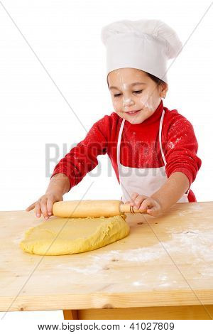 Little girl kneading the dough