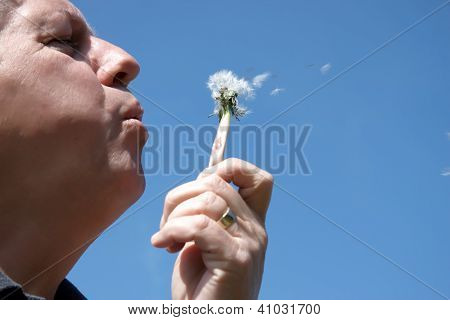A Man Blowing Seeds