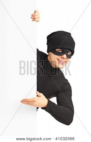 A thief with robbery mask gesturing on a blank panel isolated on white background