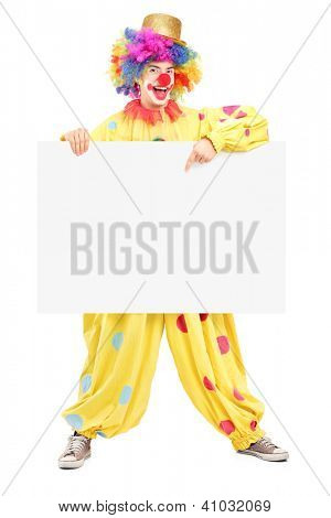 Full length portrait of a happy male clown pointing on a blank panel isolated on white background